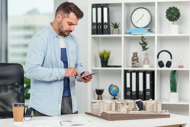 잘 생긴 엔지니어가 건설 프로젝트에 참여하고 미래 건물의 모형을 검토하고 태블릿 pc에서 메모를 작성합니다.