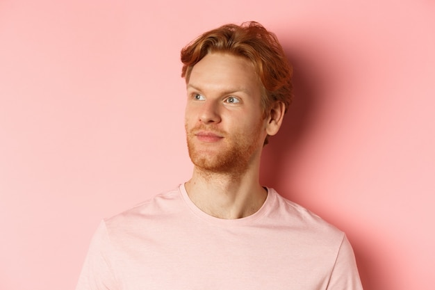 Handsome european male model with red hair and beard, turn head and looking pleased at copy space on left side, standing over pink background.
