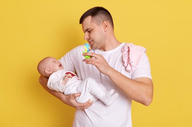 カジュアルな白いtシャツを着たハンサムなヨーロッパ人男性は、生まれたばかりの赤ちゃんと一緒に黄色い壁に立ち、小さな娘を見て、お手玉を持って子供に見せ、子供を落ち着かせようとしています。
