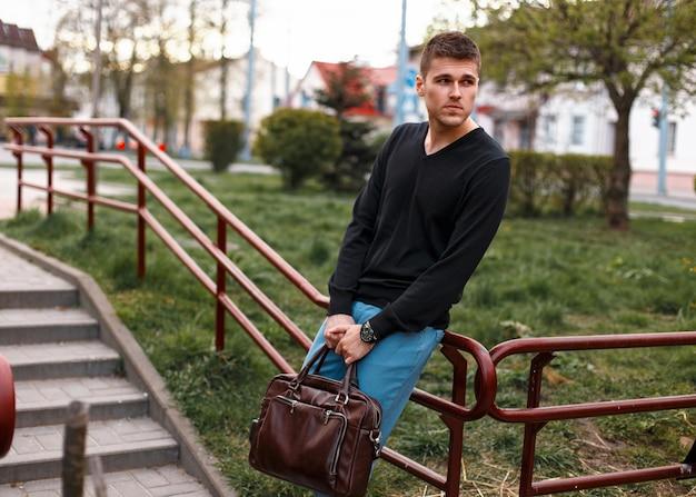 Красивый европейский мужчина с кожаной сумкой в городе