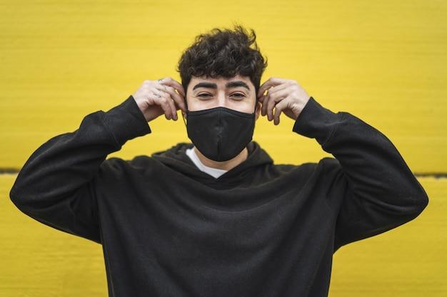 Bello pattinatore europeo in felpa con cappuccio in posa davanti a un muro giallo in un viso