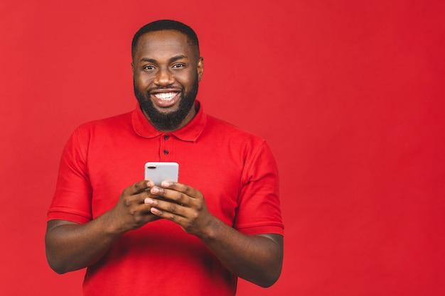 Красивый возбужденный веселый радостный афро-американский парень отправляет и получает сообщения своему возлюбленному