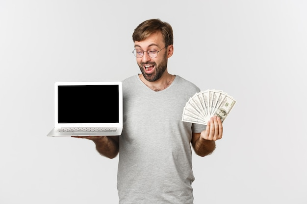 Красивый возбужденный мужчина-фрилансер, показывающий экран ноутбука и деньги
