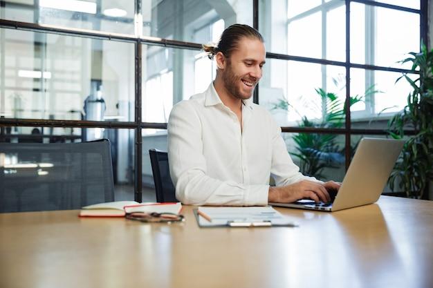 現代のオフィスのテーブルに座って笑ってラップトップで作業しているハンサムな興奮した男
