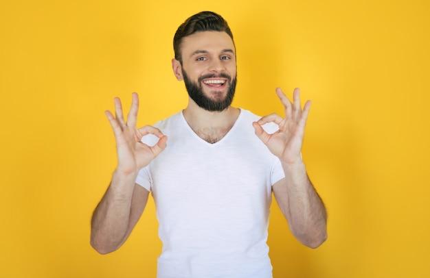 Красивый возбужденный современный молодой бородатый стильный мужчина позирует с широкой зубастой улыбкой