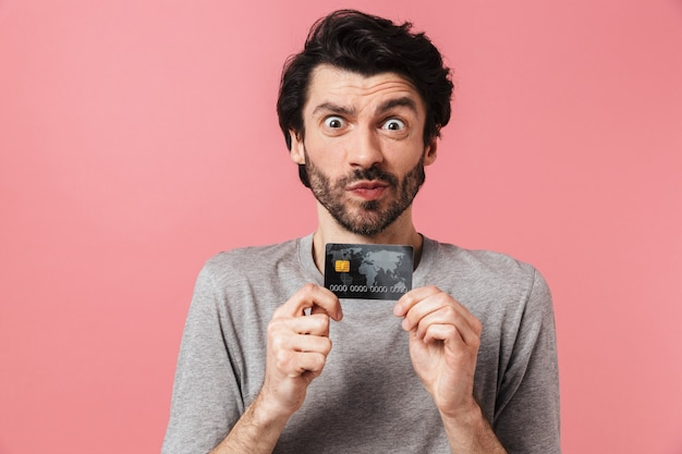Красивый возбужденный молодой бородатый брюнет в свитере стоит над розовым, показывая кредитную карту