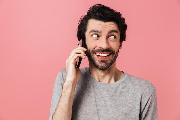 Красивый возбужденный молодой бородатый брюнет в свитере стоит над розовым, разговаривает по мобильному телефону