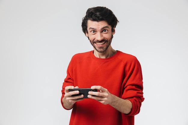 Красивый возбужденный молодой бородатый брюнет в свитере стоит над белой, играя в игры на мобильном телефоне