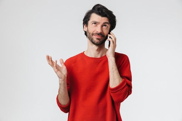 Красивый возбужденный молодой бородатый брюнет в свитере стоит над белой и разговаривает по мобильному телефону