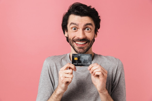 Handsome excited young bearded brunette man wearing sweater standing over pink, showing credit card