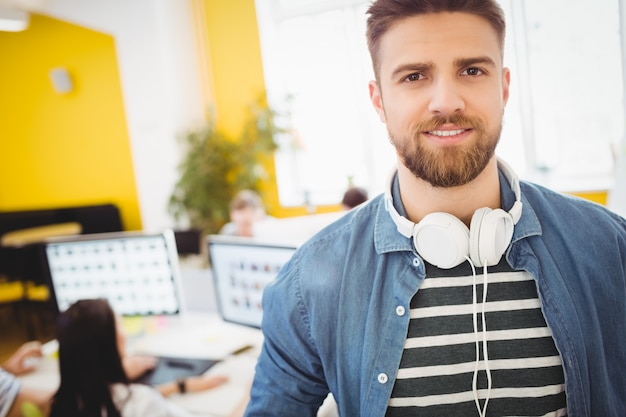 Handsome executive with headphones at creative office