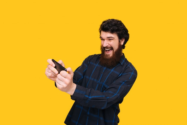 Handsome exited man playing game on smartphone over isolated yellow wall