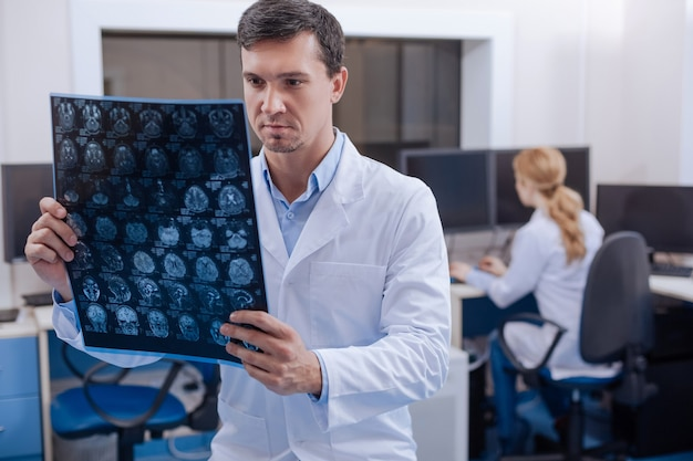 Handsome experienced nice doctor looking at an x ray image and putting a diagnosis while working in the oncology department