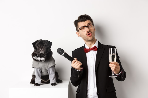 안경을 쓴 멋진 남자, 샴페인 한 잔을 들고 파티 정장을 입은 귀여운 퍼그에게 마이크를 주고 축하하고 재미, 흰색 배경