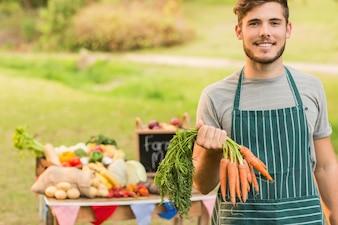 Handsome farmer holding carrots
