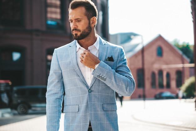 Modello di uomo d'affari moda bello vestito in elegante abito blu in posa sulla strada