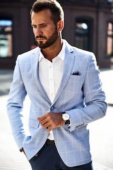 Handsome fashion businessman model dressed in elegant blue suit posing on street