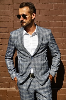 Handsome fashion businessman model dressed in elegant checkered suit posing near brick wall on the street