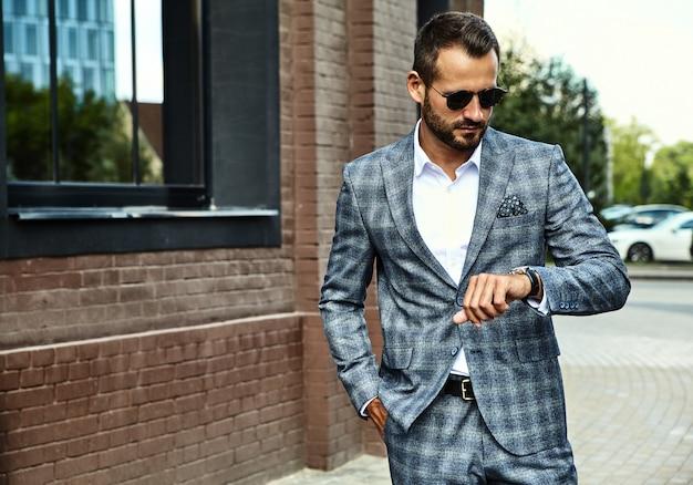 Handsome fashion businessman model dressed in elegant checkered suit posing on street