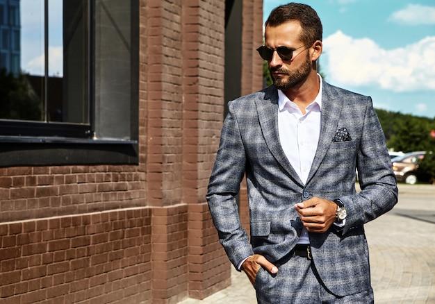 Modello di uomo d'affari moda bello vestito in elegante abito a scacchi in posa sulla strada