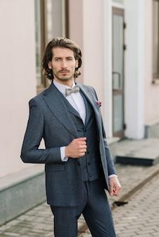 エレガントなスーツに身を包み、ストリートでポーズをとるハンサムなファッションビジネスマンモデル。メトロセクシャル