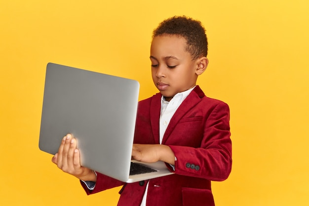 Handsome fashionable african boy keyboarding on generic portable electronic gadget messaging online via social networks, learning remotely. childhood, technology, communication and education
