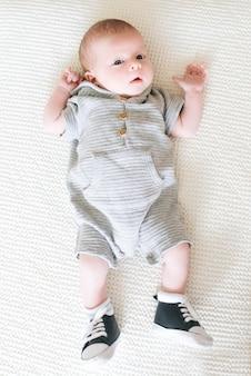 甘い表情で、毛布の上に横たわるハンサムなファッショナブルな少年