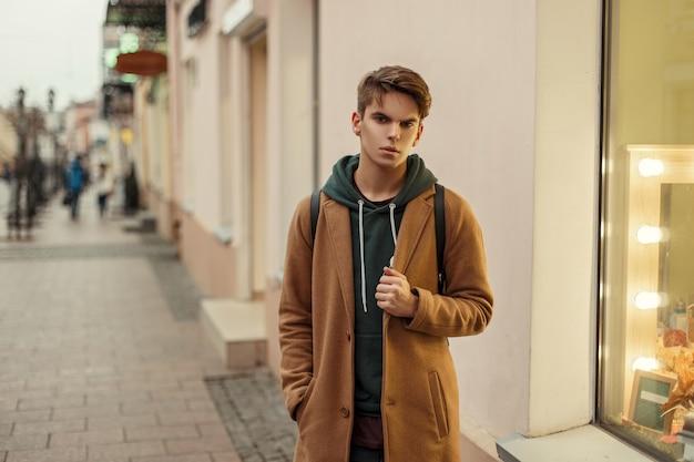 거리에 쇼케이스 근처 포즈 까마귀와 세련된 빈티지 코트에 잘 생긴 유행 남자