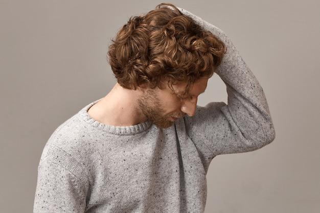Bello alla moda con la barba lunga barbuto giovane maschio caucasico con acconciatura ondulata vestito con un pullover lavorato a maglia grigio alla moda, guardando in basso e toccando i suoi capelli rossastri, con sguardo profondo nei pensieri
