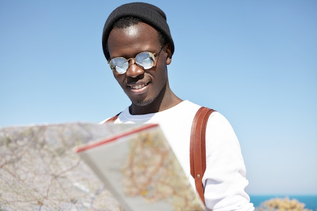 Handsome and fashionable young black tourist in round shades and headwear looking at paper map in his hands with interest, reading information about city where he is spending summer vacations in