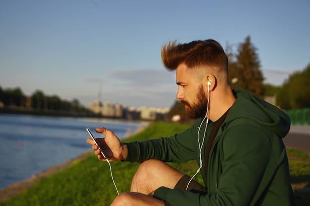 スタイリッシュな髪型と厚いひげを持つハンサムなファッショナブルな若い男は、屋外で穏やかな夏の朝を楽しんで、湖のそばに座って、彼の携帯電話のオンラインアプリを使用して音楽トラックを聴いています