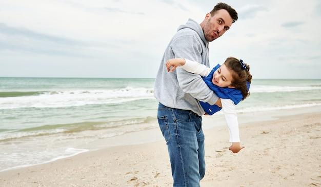 그의 작은 귀여운 딸을 팔에 안고 해변에서 함께 노는 잘생긴 아버지.
