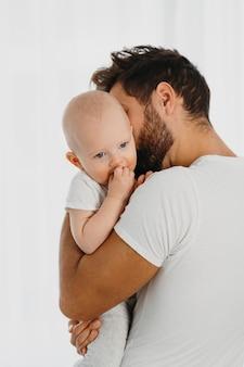 Padre bello che tiene e che bacia il suo bambino