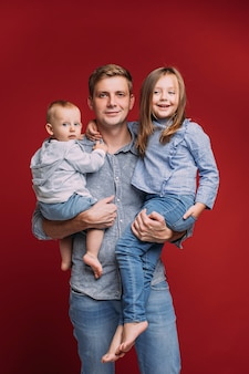 Handsome father holds two his children on his hands