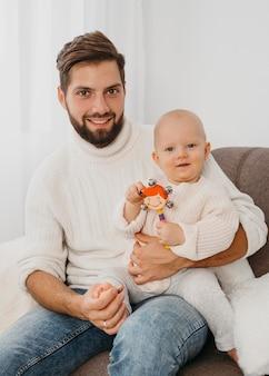 赤ちゃんと一緒にソファでポーズをとるハンサムな父