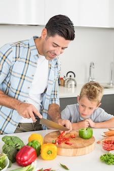 야채를 자르는 방법 그의 아들을 가르치는 잘 생긴 아버지
