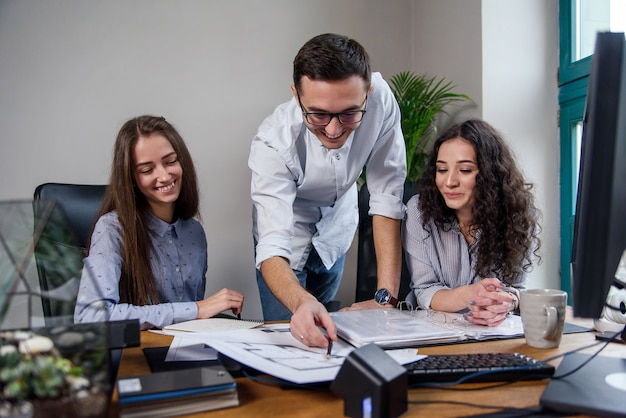 Handsome firm manager in glasses explains work tasks for his employees. creative people or advertising business concept. team work. young beautiful people working in office together.