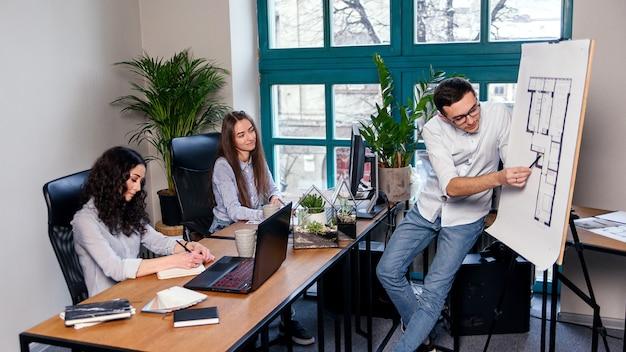 メガネをかけたハンサムな会社のマネージャーが、彼の従業員の仕事のタスクを説明しています。創造的な人々または広告ビジネスコンセプト。チームワーク。一緒にオフィスで働く美しい若者。