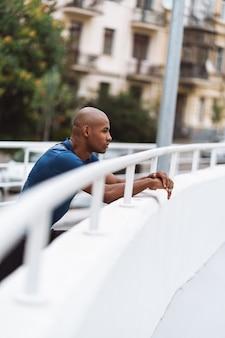 屋外でのトレーニングの後、レールに寄りかかって休んでいるハンサムなフィットのアフリカのフィットネス男