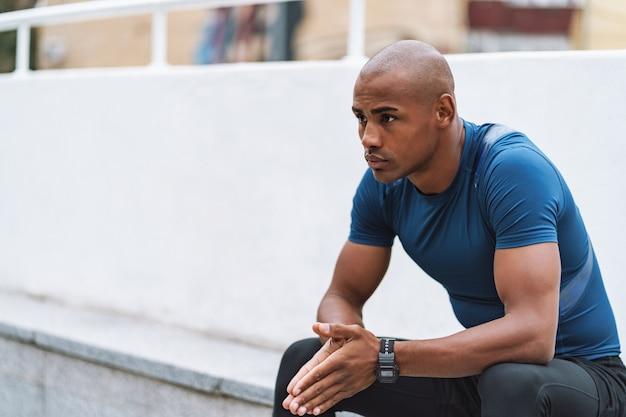 屋外でのトレーニングの後、座って休んでいるハンサムなフィットのアフリカのフィットネス男