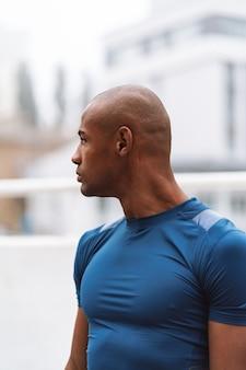 屋外でのトレーニングの後、立って、目をそらして休んでいるハンサムなフィットのアフリカのフィットネス男