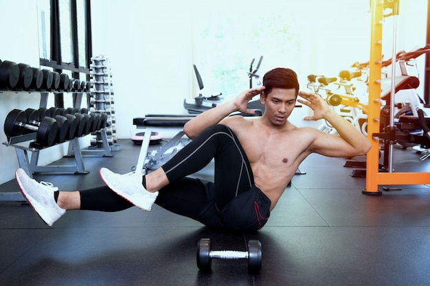 Handsome fit man doing crunches at gym