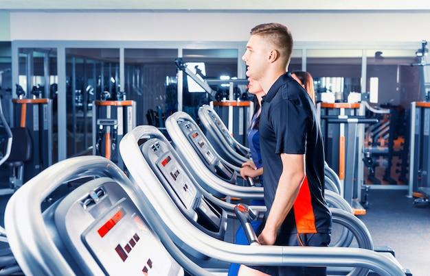 Красивый мужчина тренируется на беговой дорожке в ярком современном тренажерном зале
