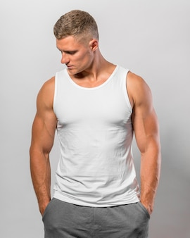 Handsome fit man posing while wearing tank top