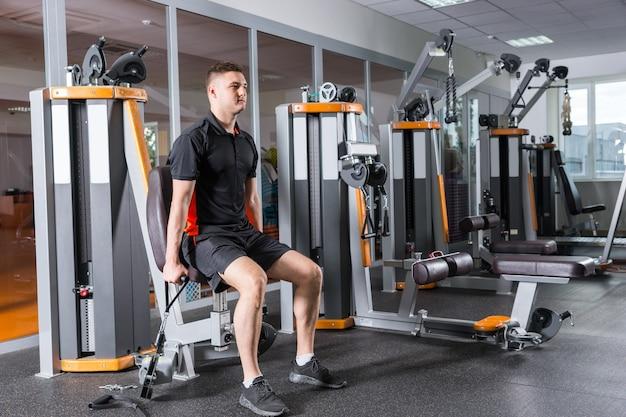 現代のマシンでトレーニングし、フィットネスセンターのジムルームで運動するハンサムなフィットの男