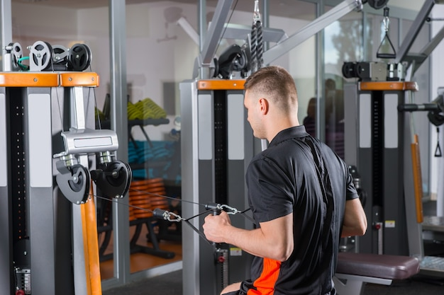 フィットネスセンターのジムルームでローイングマシンでトレーニングするハンサムなフィット男