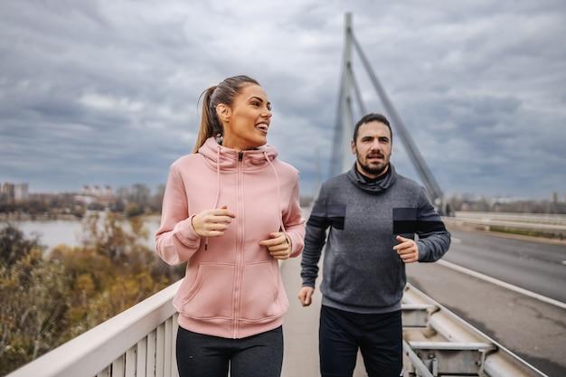 橋の上をジョギングしているスポーツウェアでハンサムなフィットのスポーティな異性愛者の友人。アーバンエクステリア。フィットネス屋外コンセプト。