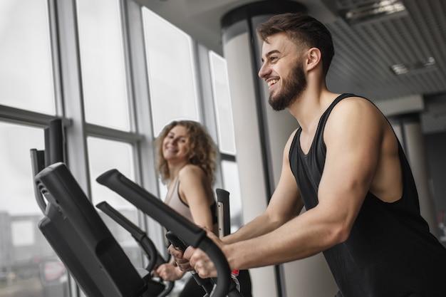 Красивый инструктор по фитнесу вместе со своим привлекательным клиентом тренируется на велотренажере в тренажерном зале