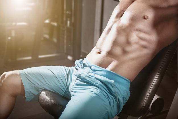 ハンサムなフィットネス男ジムで重量挙げトレーニング