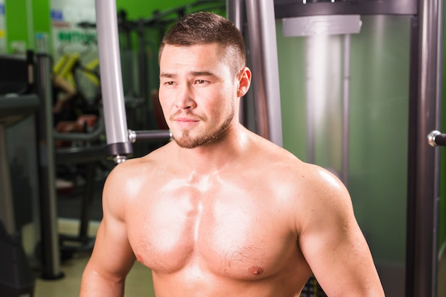 Handsome fitness man works out in gym